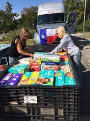 Simone Calvas of Dearborn and Cindy Curto of Grosse Ile pack some of the donations made to Grosse Ile Bridge to Texas. The semi from Northfield Trucking of Taylor ultimately transported the goods to Houston.