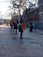 Coats and sweaters hang from trees in downtown Nashville.