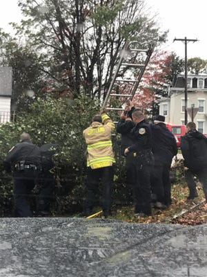 Firefighters and police help a SUNY Cortland student who became trapped under an uprooted tree.