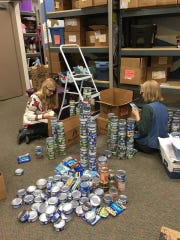 Volunteers stock the shelves with canned goods at Soup