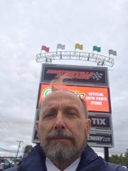 Gene Stilp takes a selfie at a NASCAR race in Alabama as he prepares to burn a two-sided Confederate-Nazi flag.