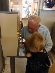Norm Immel helps a young patron get a special treat from the candy machines at Connie's Diner.