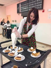 Bank employee Amanda Nicholson topped off pumpkin and pecan pies at the dessert table.