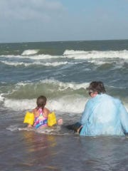 The author and her granddaughter play in the Texas surf on a vacation to the coast.