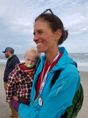 Jennifer Pharr Davis holds son Gus at the end of Mountains-to-Sea Trail at Jockey's Ridge State Park.