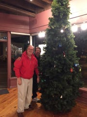 Guests attending Chincoteague's Homes for the Holidays tour this Saturday are encouraged to bring new hats, mittens, scarves, gloves and socks to decorate the Warm Hands, Warm Hearts tree inside the Island Theatre Annex, pictured with Bill Baals and Joe Ficchi.