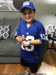 Jayden Perez holds a bobble head doll of New York Giants