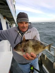An angler with a triggerfish landed on the Dauntless
