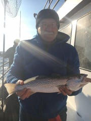 A fishermen holds a weakfish he caught bottom fishing