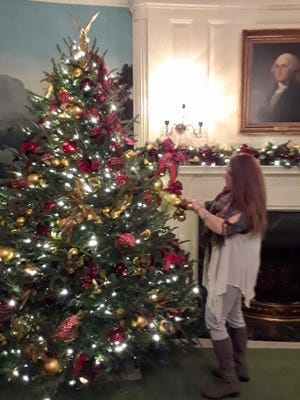Dallastown native Debra Eberly hangs ornaments and ribbon on a Christmas tree in the Diplomat Room of the White House. Eberly was one of about 100 volunteers chosen to decorate the White House for Christmas in 2017.