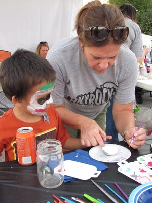 Jo Price Craven helps a youngster paint a rock at the Boone County Sheriff's Night Out event in September.