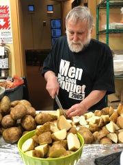 Ira Karasick cuts potatoes to make latkes for the annual