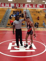 Referee Smith Isme raises Immokalee 126-pounder Gabriel Ramirez's hand in victory at the Collier County Athletic Conference wrestling championships on Saturday at the Indians' gym.
