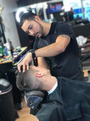 Anthony Arenivar shows off some of his barber skills.