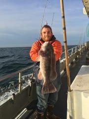 Brendan Skerletts holds up a blackfish he caught on