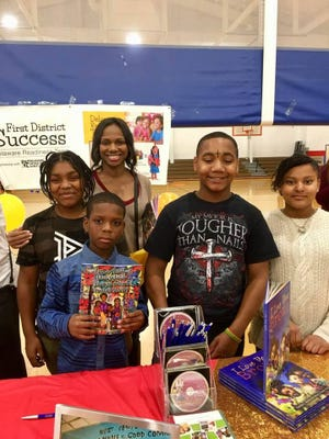 "The authors of ""Football, Basketball, Lost at School, Peanut Butter"" — Artie Melton, Debra Smith, Gordon Byrd, Jamar Kelson and Quinnell Anderson — posed for photos and signed copies of their book during a community day in December."