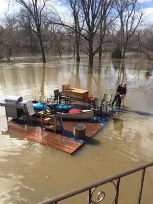John Estill stands next to his deck after it floated away from his home and into the flood waters of the Grand River on Thursday, Feb. 22.