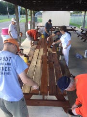 Members of the Coshocton Rotary Club stain picnic tables at the Rotary Shelter behind Kids America. Counterclockwise are Eric Taggart, Tom Bryan, Gordon Spillman, Bob Pell, Todd Brown, Valerie Miller, Barb Emmons and Steve Miller.