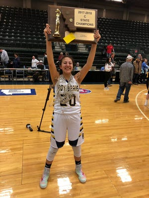 Box Elder's Lilly Gopher holds the State Class C championship trophy earlier this month at the Butte Civic Center. The red ribbons on her shoes indicate her involvement with Missing and Murdered Indigenous Women.