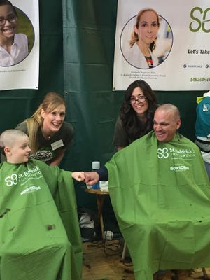 Volunteer barbers Becki Stapleton and Noel O'hare along with shavees Aaron Buerstetta and his nephew, R-L Wynton, return each year for the St. Baldrick's Day event at the North Plainfield Fire Department.