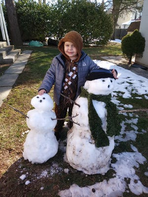 Caelan Hoisington, 6, Annville, with his snowmen.  The larger snowman, which was built by Hoisington and his family, was kicked over by someone the day it was built, March 22. Officer Jason Cleck of the Annville Township Police Department rebuilt the snowman and built a second snowman for Hoisington.