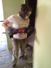 Linsey Higgins using a reciprocating saw to remove