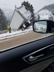 A semi truck dangles off the east side of Rogers Pass