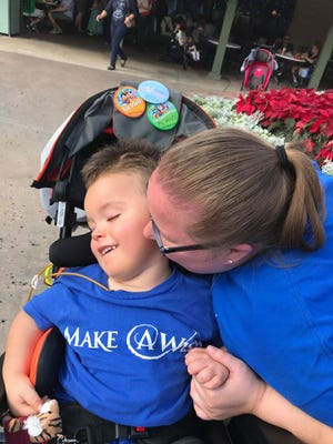 Ben gets a kiss from his mom, Jamie Welser, during his Make a Wish trip to Disney World.