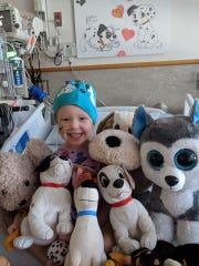 Julie Hildebrand is surrounded by puppy love in her room at Children's Hospital of Philadelphia