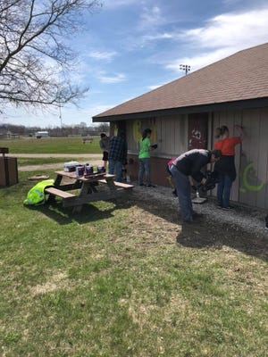 Students from Gibsonburg High School cover over racist graffiti painted on a shelter at Williams Park.