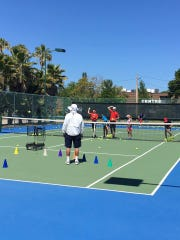 Gerry Berkheimer, director of tennis at the Jungle Club, oversees a game played during the recent 12-hour marathon to raise money for the Hope for Families.