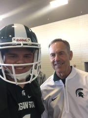 "Mike Sterner (left) and Michigan State head football coach, Mark Dantonio, smile for a selfie during one of ""Sparty Mike's"" many trips to Spartan Stadium since he has became a student in 2012."