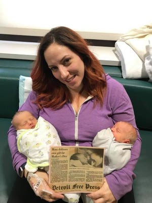 Andrea Zarzecki, born on Mother's Day May 12, 1985, holding her newborn twins, Charles and Penny, as well as the Free Press article of her birth, on Mother's Day 2018.