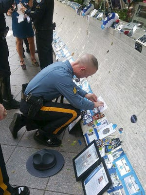 Delaware State Police Sgt. Christopher Martin sketches the name of Cpl. Stephen Ballard this week at the memorial for fallen officers in Washington, D.C.