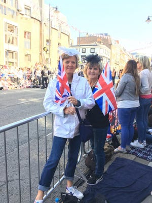 Janie Gasser (left) and Liz Whittern wait along the royal wedding parade route for a look at the now Duke and Duchess of Sussex.