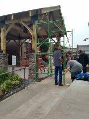 Scaffolding is set in place as masonry and carpentry
