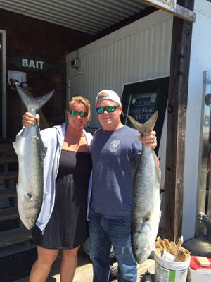 At Lewes Harbour Marina, Jules and Billy Mister hold bluefish that they caught at the Cape Henlopen State Park fishing pier.