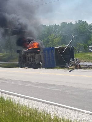 A semi-truck lays on its side, burning on June 5.