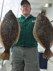 An angler with a pair of fluke caught on the Jamaica