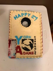 A cake in the shape of a cornhole board celebrates the two-year anniversary of York Adams Cornhole, a league dedicated to the leisure game often played at tailgates.