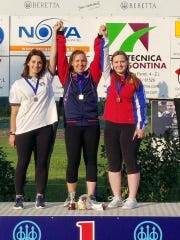 Madelynn Bernau (center) stands on the podium May 20 after winning the gold medal in trapshooting at the International Junior Grand Prix in Porpetto Italy.