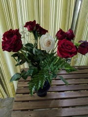 A bouquet of roses, including one white rose for Officer