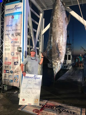 Angler Connor Ferrara, of the Pensacola fishing team Reel Fire, poses with a 665-pound Blue Marlin caught at the Emerald Coast Blue Marlin Classic on Saturday in Miramar Beach.