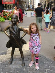 "Zoey poses next to ""Fearless Girl"" statue in New York"