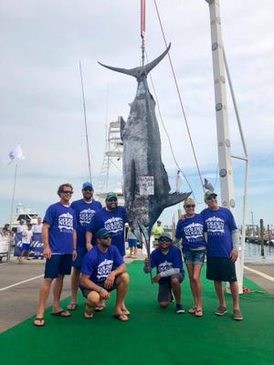 Anglers stand with a massive blue marlin at the 2017 Blue Marlin Grand Championship.