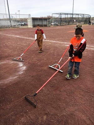 Members of the Aztec Legends youth baseball team clean up a field in Aztec as part of their service for the Volunteer Incentive Program.