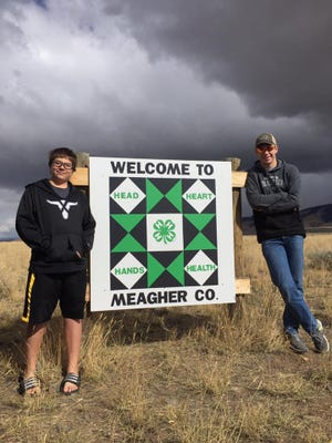The Hansons pose with a 4-H themed block that is part of the Art and Cultural Trail project sponsored by the Meagher County Chamber of Commerce. Barn quilts have been made around the county.