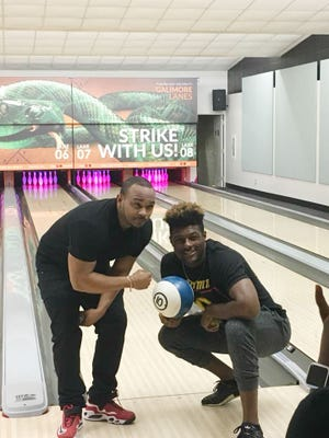 Kayvon Thibodeaux (left) hits a strike in the bowling alley at FAMU.