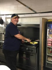 Don Larson cooks eggs on Saturday morning during the