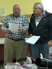 Lions Club members Howard Moran, left, and Myrle Patridge, right, check lists of items that need to be arranged for the Lions Club Auction.